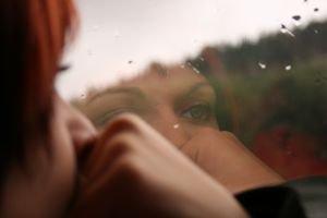 Imagem-de-mulher-sendo-refletida-numa superficie-a-sua-frente-tendo-o-rosto-apoiado-em-uma-das-maos1
