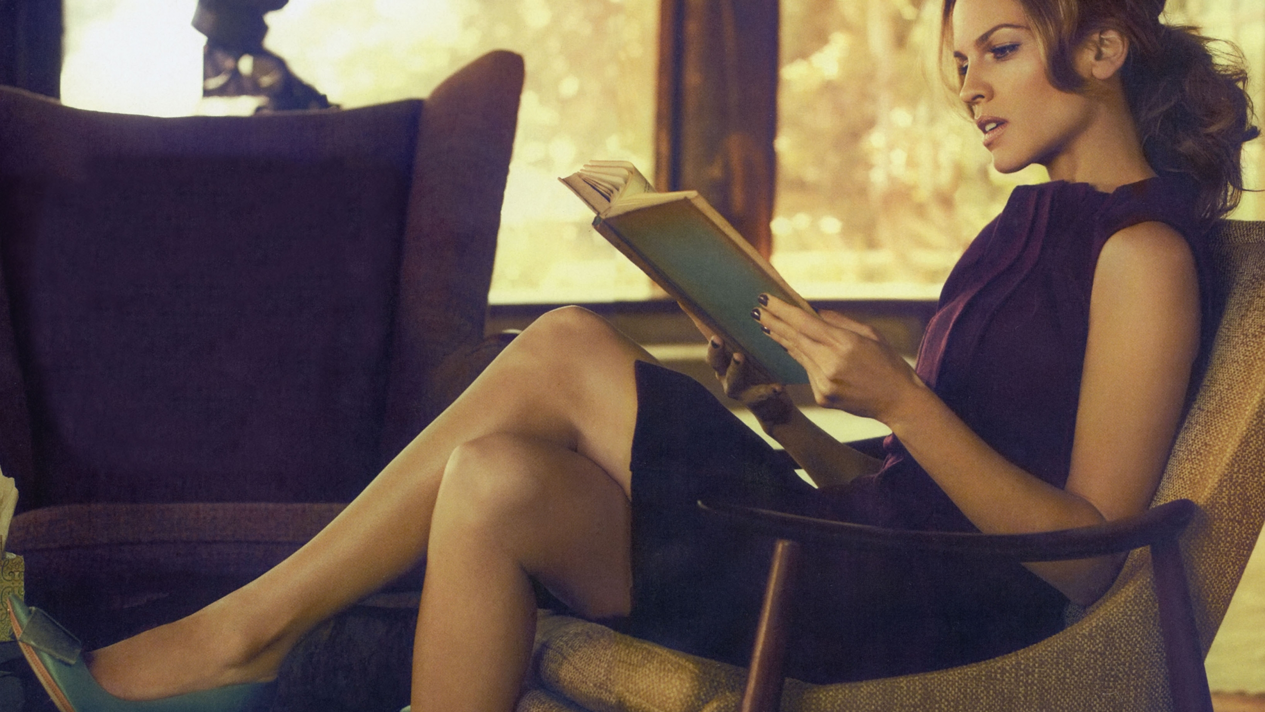 beautifull-actress-hilary-swank-reading-a-book-in-chair-hd-mobile-2080169